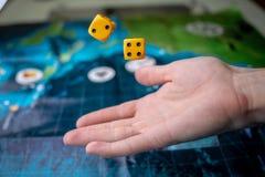 Το χέρι ρίχνει κίτρινο χωρίζει σε τετράγωνα στο αγωνιστικό χώρο Τύχη και ενθουσιασμός Επιτραπέζια παιχνίδια Στιγμές τυχερού παιχν στοκ εικόνα με δικαίωμα ελεύθερης χρήσης