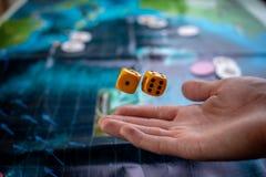 Το χέρι ρίχνει κίτρινο χωρίζει σε τετράγωνα στο αγωνιστικό χώρο Τύχη και ενθουσιασμός Έννοια των επιτραπέζιων παιχνιδιών Στιγμές  στοκ εικόνα
