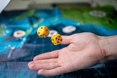 Το χέρι ρίχνει κίτρινο χωρίζει σε τετράγωνα στο αγωνιστικό χώρο Τύχη και ενθουσιασμός Έννοια των επιτραπέζιων παιχνιδιών Στιγμές  στοκ εικόνα με δικαίωμα ελεύθερης χρήσης