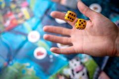 Το χέρι ρίχνει κίτρινο χωρίζει σε τετράγωνα στο αγωνιστικό χώρο Τύχη και ενθουσιασμός Έννοια των επιτραπέζιων παιχνιδιών Στιγμές  στοκ φωτογραφία με δικαίωμα ελεύθερης χρήσης