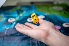 Το χέρι ρίχνει κίτρινο χωρίζει σε τετράγωνα στο αγωνιστικό χώρο Τύχη και ενθουσιασμός Έννοια των επιτραπέζιων παιχνιδιών Στιγμές  στοκ εικόνες με δικαίωμα ελεύθερης χρήσης