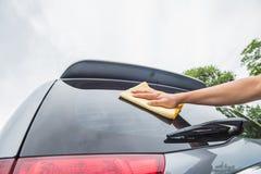 Το χέρι σκουπίζει το καθαρίζοντας γυαλί αυτοκινήτων στοκ εικόνες