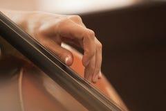 Το χέρι στις σειρές ενός βιολοντσέλου Στοκ φωτογραφίες με δικαίωμα ελεύθερης χρήσης