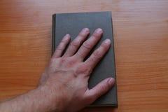 Το χέρι στο βιβλίο στοκ εικόνες με δικαίωμα ελεύθερης χρήσης