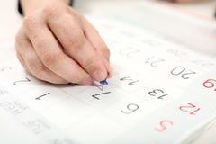 Το χέρι συνδέει την καρφίτσα σε 7ο του μήνα στο ημερολόγιο στοκ φωτογραφία με δικαίωμα ελεύθερης χρήσης