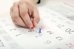 Το χέρι συνδέει την καρφίτσα στο ημερολόγιο στοκ εικόνες