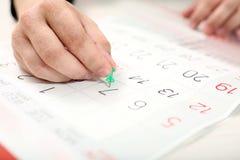 Το χέρι συνδέει την πράσινη καρφίτσα σε 7ο του μήνα στο ημερολόγιο στοκ φωτογραφία με δικαίωμα ελεύθερης χρήσης