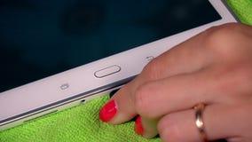 Το χέρι συνδέει το καλώδιο με τη συσκευή υπολογιστών ταμπλετών στο πράσινο υπόβαθρο απόθεμα βίντεο