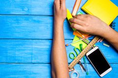 το χέρι σχολικών σπουδαστών καθαρίζει μακριά τις σχολικές προμήθειες στο μπλε ξύλινο επιτραπέζιο υπόβαθρο ο σπουδαστής προτιμά να στοκ φωτογραφία με δικαίωμα ελεύθερης χρήσης