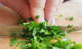 Το χέρι τεμάχισε τον πράσινο τεμαχισμένο μαϊντανό στο εσωτερικό επιτραπέζιων κουζινών Στοκ Εικόνες