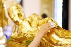 Το χέρι της ασιατικής γυναίκας κολλά το χρυσό φύλλο στο χρυσό ξαπλώνοντας Βούδα stutue στοκ εικόνα με δικαίωμα ελεύθερης χρήσης