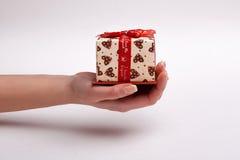 Το χέρι της γυναίκας δίνει ένα όμορφο κιβώτιο δώρων με ένα τόξο Στοκ Εικόνες