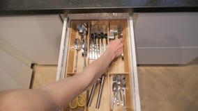 Το χέρι της γυναίκας ανοίγει το συρτάρι κουζινών με τα μαχαιροπήρουνα μέσα απόθεμα βίντεο