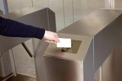 Το χέρι της γυναίκας βάζει την άσπρη πλαστική κάρτα στα clos αναγνωστών Στοκ Φωτογραφία