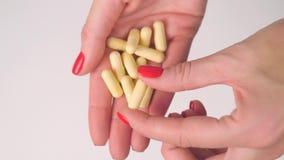 Το χέρι της γυναίκας δίνει τα κίτρινα χάπια καψών απόθεμα βίντεο