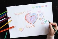 Το χέρι της γυναίκας επισύρει την προσοχή τις καρδιές μολυβιών σε χαρτί για στενό επάνω ημέρας του βαλεντίνου στοκ εικόνα
