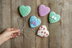 Το χέρι της γυναίκας κρατά τις καρδιές μελοψωμάτων για τις σειρές όπως τα μπαλόνια στοκ εικόνα