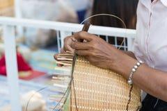 Το χέρι της γυναίκας κρατά ότι οι χωρικοί πήραν τα λωρίδες μπαμπού στην ύφανση σε διαφορετικό Στοκ Εικόνα
