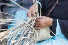 Το χέρι της γυναίκας κρατά ότι οι χωρικοί πήραν τα λωρίδες μπαμπού στην ύφανση Στοκ Εικόνες