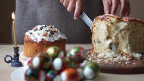 Το χέρι της γυναίκας κόβει ένα εορταστικό Πάσχα στον πίνακα κουζινών δίπλα σε ένα κερί εκκλησιών φιλμ μικρού μήκους