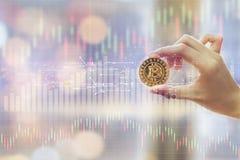 Το χέρι της γυναίκας που κρατά ένα χρυσό Bitcoin είναι ψηφιακό νόμισμα, και παρουσιάζει γραφική παράσταση με τη γραφική παράσταση Στοκ εικόνες με δικαίωμα ελεύθερης χρήσης