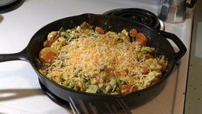 Το χέρι της γυναίκας προσθέτει το τυρί στα αυγά προγευμάτων και τα λαχανικά και τα μίγματα φιλμ μικρού μήκους