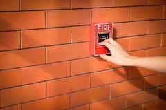 Το χέρι της γυναίκας τραβά το συναγερμό πυρκαγιάς στο τουβλότοιχο στοκ φωτογραφίες