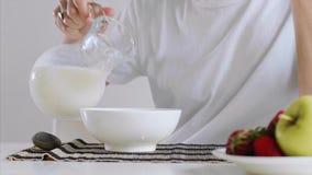 Το χέρι της γυναίκας χύνει το γάλα και τα δημητριακά σε ένα κύπελλο για το πρόγευμα απόθεμα βίντεο