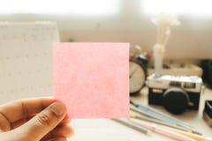 Το χέρι της επιχειρηματία που κρατά μετα αυτό τη σημείωση με τη κάμερα και το ημερολόγιο τοποθέτησε το υπόβαθρο εικόνα για τον ερ Στοκ εικόνα με δικαίωμα ελεύθερης χρήσης