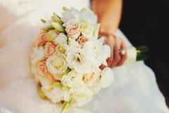 Το χέρι της νύφης κρατά μια γαμήλια ανθοδέσμη των άσπρων και κρεμωδών τριαντάφυλλων Στοκ Εικόνες