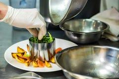 Το χέρι του αρχιμάγειρα προσθέτει τη σαλάτα στις σφήνες πατατών στο πιάτο στοκ φωτογραφίες