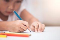 Το χέρι του ασιατικού κοριτσιού παιδιών σύρει και χρωματίζει με το κραγιόνι Στοκ φωτογραφία με δικαίωμα ελεύθερης χρήσης