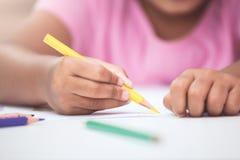 Το χέρι του ασιατικού κοριτσιού παιδιών σύρει και χρωματίζει με το κραγιόνι Στοκ Φωτογραφίες