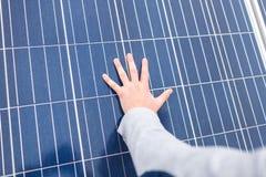 Το χέρι του ατόμου βρίσκεται στην επιτροπή μιας ηλιακής μπαταρίας Στοκ φωτογραφίες με δικαίωμα ελεύθερης χρήσης