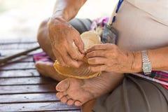 Το χέρι του ατόμου κρατά ότι οι χωρικοί πήραν τα λωρίδες μπαμπού στην ύφανση Στοκ Εικόνες