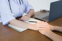 Το χέρι του γιατρού καθιστά τον αρσενικό ασθενή βέβαιο στοκ φωτογραφία με δικαίωμα ελεύθερης χρήσης