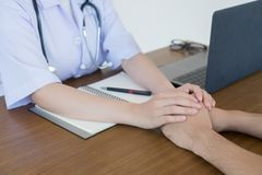 Το χέρι του γιατρού καθιστά τον αρσενικό ασθενή βέβαιο στοκ εικόνες