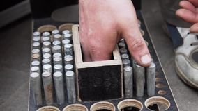 Το χέρι του εργαζομένου ατόμων βάζει τις κυλινδρικές μεταλλικές καρφίτσες στο ξύλινο κιβώτιο με τις στρογγυλές τρύπες απόθεμα βίντεο