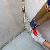 Το χέρι του εργαζομένου καθορίζει ένα μίσθωμα στον τοίχο χρησιμοποιώντας τον αφρό πολυουρεθάνιου στοκ εικόνα