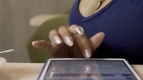 Το χέρι του θηλυκού, που δακτυλογραφεί messeges στην ταμπλέτα της στον καφέ, κλείνει επάνω φιλμ μικρού μήκους