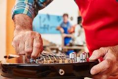 Το χέρι του κατασκευαστή κιθάρων ρυθμίζει το γαλλικό κλειδί Στοκ Εικόνες