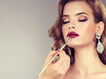 Το χέρι του κυρίου σύνθεσης χρωματίζει τα χείλια του νέου όμορφου προτύπου brunette στοκ φωτογραφία με δικαίωμα ελεύθερης χρήσης