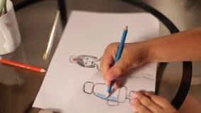 Το χέρι του παιδιού επισύρει την προσοχή το θηλυκό γιατρό στο μπλε μολύβι σε χαρτί απόθεμα βίντεο