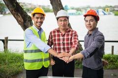 Το χέρι τρία των μηχανικών παίρνει το συντονισμό για κάνει μια συμφωνία στην επένδυση για το σπίτι και την κατοικία στοκ φωτογραφίες