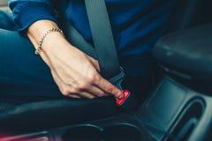 Το χέρι των ατόμων στερεώνει τη ζώνη ασφαλείας του αυτοκινήτου Κλείστε το κάθισμα αυτοκινήτων σας στοκ εικόνες