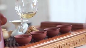 Το χέρι των γυναικών χύνει ήπια σε τέσσερα φλυτζάνια του ευώδους τσαγιού από teapot γυαλιού απόθεμα βίντεο