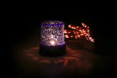 Το χέρι φθάνει για έναν όμορφο λαμπτήρα νύχτας στο σκοτάδι Στοκ Εικόνες