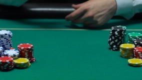 Το χέρι φορέων που ρίχνει το ζευγάρι των άσσων στον πίνακα, κερδίζει το συνδυασμό, στοίχημα πόκερ, επιτυχία απόθεμα βίντεο