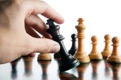 Το χέρι φορέων ` s σκακιού κρατά το κομμάτι σκακιού του μαύρου βασιλιά Στοκ Εικόνες