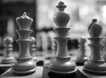 Το χέρι χάρασε, ξύλινα κομμάτια σκακιού που είδαν σε έναν πίνακα σκακιού πληγών ανταγωνισμού Στοκ Εικόνα